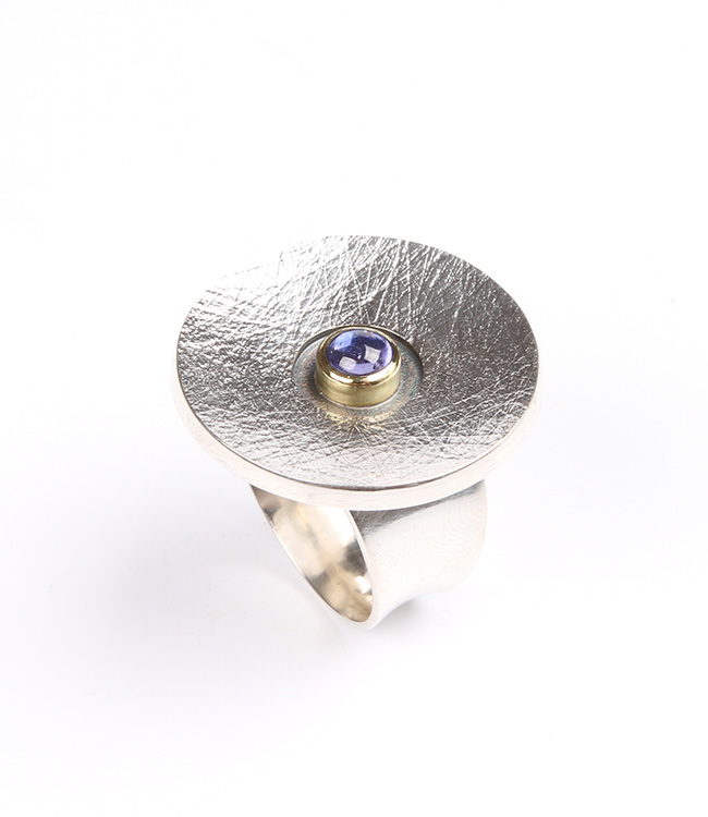 Big silver ring with a lilac sapphire.