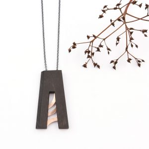 Small pendant made of ebony wood and red gold