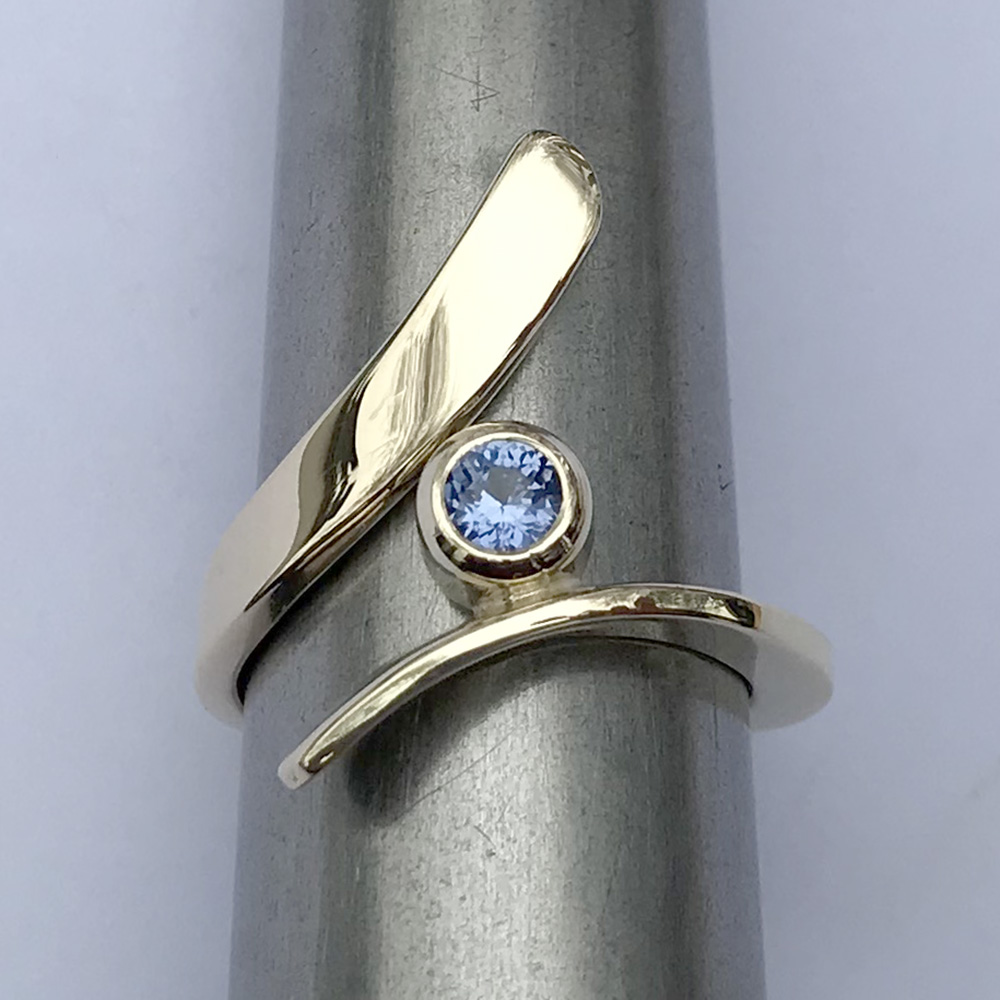 Hand forged gold ring with a blue sapphire